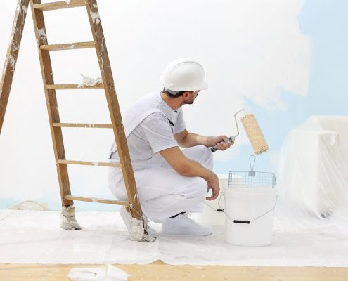 a painter applying decorative coating on interior wall