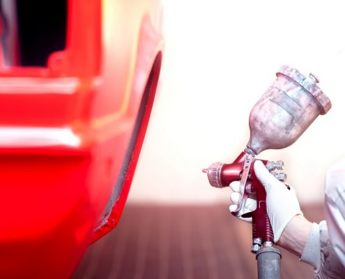 vehicle powder coating being applied on a red car