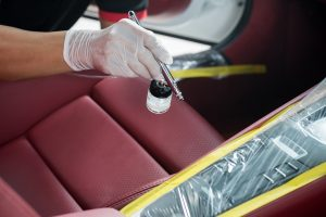 an automotive interior coating spray being applied on masked interior