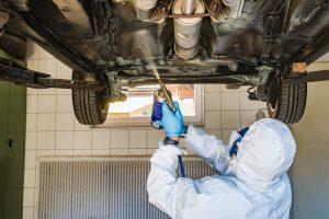 applying automotive underbody coating with a spray gun to a car bottom